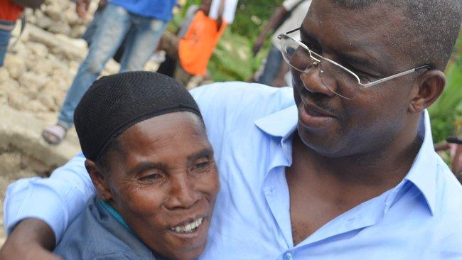 Haitian Senator Rony Celestin hugging a woman in Plateau Central Haiti