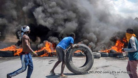 Haitian protesters in the street setting a lot of tires on fire